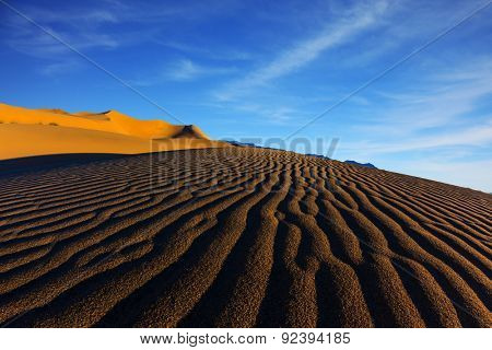 Sand dunes in Death Valley, USA. The contrast of light and shadow on the waves of sand in the morning at sunrise.