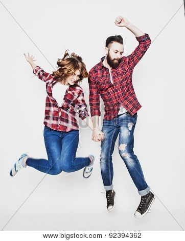 life style, happiness and people concept: Happy loving couple. Jumping over light grey background. Special Fashionable toning.
