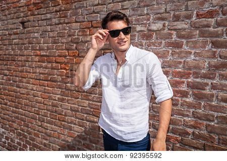 Smiling young fashion man looking away from the camera while fixing his sunglasses.