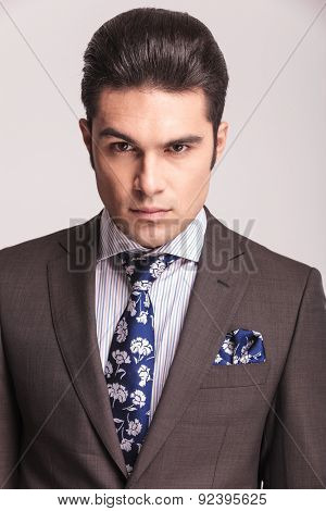 Portrait of a elegant business man wearing a grey suit and blue tie.