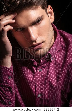 Close up picture of a handsome young man thinking while looking down.