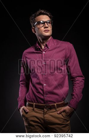 Attractive young fashion man looking up while holding his hands in pockets.