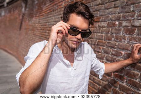 Handsome young man leaning on a brick wall while taking off his sunglasses.
