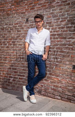Attractive young man posnig with his hands in pockets while leaning on a brick wall/