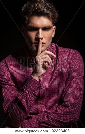 Attractive young casual man making the silence gesture while looking at the camera.