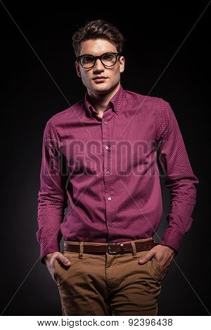 Handsome casual man looking at the camera while holding his hands in pockets.