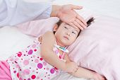 stock photo of forehead  - Sick little girl nursed by a pediatrician doctor touching forehead little asian girlgirl lying with digital mercury thermometer - JPG