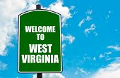 pic of virginia  - Green road sign with greeting message Welcome to WEST VIRGINIA against clear blue sky background with available copy space - JPG