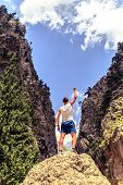 pic of mountain-climber  - Happy climber hiker or trail cross country runner reaching life goal success man at summit business concept - JPG