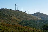 image of wind-farm  - Wind Turbines on a modern windmill farm for alternative energy production. Electricity is powered ecological and considered better for the environment over oil and other fossil fuels. A renewable resource for energy. - JPG