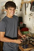 foto of workbench  - Teenage Boy Using Workbench In Garage - JPG