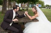 picture of wrestling  - Young happy newly wed couple fighting in arm wrestling - JPG
