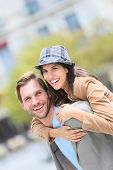 picture of piggyback ride  - Young man giving piggyback ride to girlfriend in town - JPG