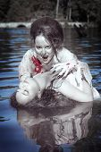 picture of bloody  - Beautiful vampire woman dressed white bloody shirt and her victim standing in the river - JPG