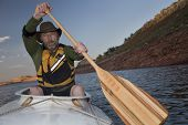 picture of mature adult  - mature male paddling a white decked expedition canoe with wooden paddle on mountain lake with red sandstone cliffs  - JPG