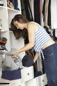 foto of wardrobe  - Teenage Girl Choosing Clothes From Wardrobe In Bedroom - JPG