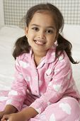 stock photo of pajamas  - Young Girl Wearing Pajamas Sitting On Bed - JPG