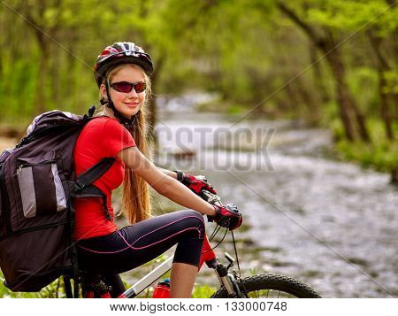 Bikes cycling girl. Girl with big rucksack rides bicycle. Girl cycling fording throught water . Cycling trip is good for health. Cyclist is looking at camera.