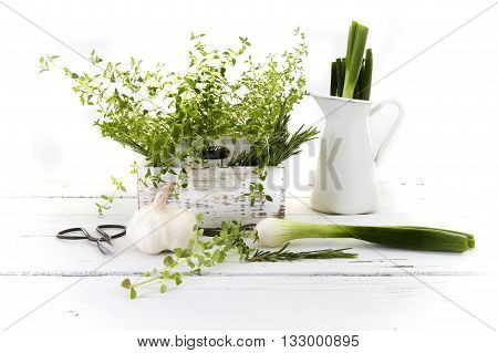 Fresh cut garden herbs (rosemary thyme parsley Garlic spring onions) in white wooden box on wooden kitchen table