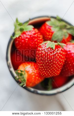 Fresh juicy strawberries in old rusty mug. Rustic wooden background with homespun napkin. Top view place for text.