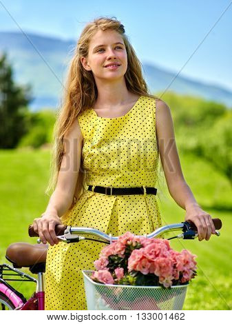Bikes bicycle girl. Teenager girl wearing dress keeps bicycle with flowers basket. Lot of green grass and tree in park.
