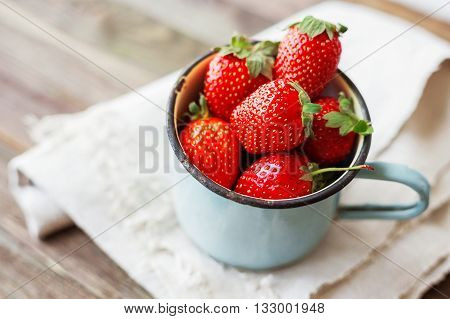 Fresh juicy strawberries in old rusty mug. Rustic wooden background with homespun napkin.
