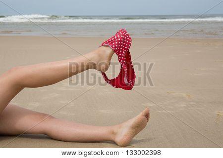 Woman on Beach holding bikini with her leg