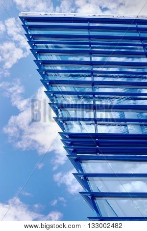 Part of modern glass construction against cloudy sky at sunny day with sky reflection