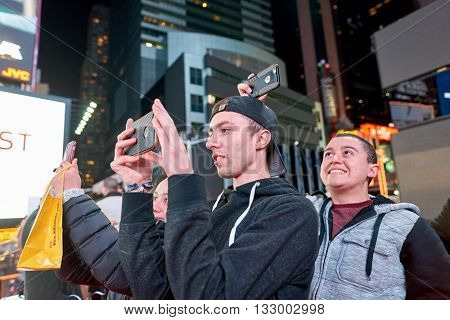 NEW YORK - CIRCA MARCH, 2016: people taking photos in New York at nighttime. The City of New York, often called New York City or simply New York, is the most populous city in the United States
