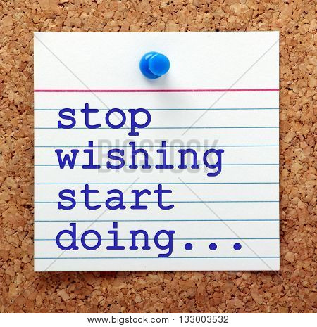 The words Stop Wishing Start Doing in blue text on a note pinned to a cork notice board as a reminder