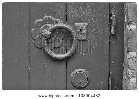 A metal blue painted latch on a blue painted wooden door. Black and white photo with a vintage border