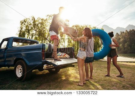 Group of young friends on picnic by the lake. Men and women unloading pickup truck on camping trip carrying picnic basket and inflatable tube on sunny day.