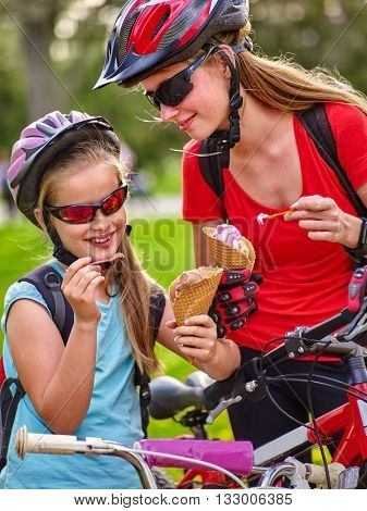 Bikes bicyclist girl. Girls wearing bicycle helmet with rucksack rides bicycle. Girls children are bicycling in summer park. Happy girls biking eating ice cream cone .