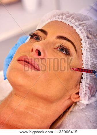 Woman middle-aged in spa salon with beautician. Beauty woman giving  injections. Spa procedure for middle-aged woman.