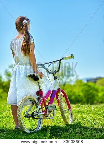Bikes bicycle girl. Child girl wearing white skirt looks into distance keeps bicycle. Blu sky and green tree on background. Summer park outdoor.