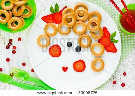 Girl face dessert or breakfast for of kids - bagels with fruit and berries cranberry juice. Picture on a plate fun with food concept