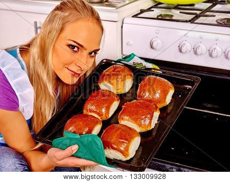 Young blond smilig woman bake cookies at kitchen. Woman waiting husband cooking bake at kitchen.