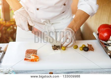 Hand with knife cuts olive. Shrimp on white cooking board. Chef working at the table. Work is in full swing.