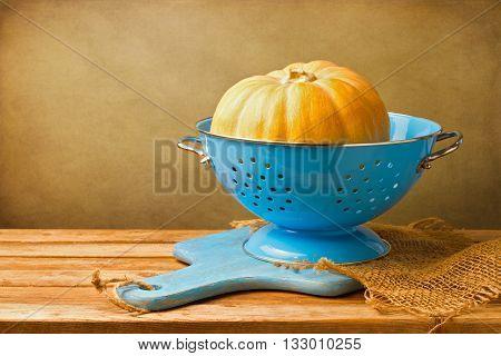 Pumpkin in blue colander on wooden tabletop against grunge wall