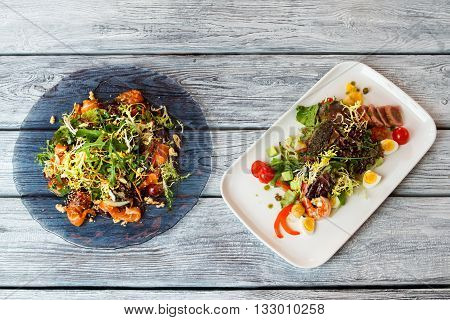 Plates with salads. Salads with herbs and seafood. Roasted shrimp and fresh salmon. Best dishes in european restaurant.