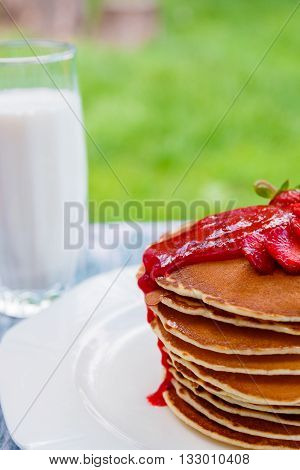 Pancakes with fresh strawberry and jem near glass with milk on white plate on white wooden background in garden or on nature background. Stack of pancakes on the table.