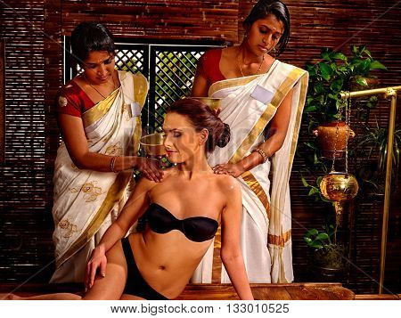 Woman having Ayurvedic spa massage treatment. Pouring oil. Spa massage with two person.