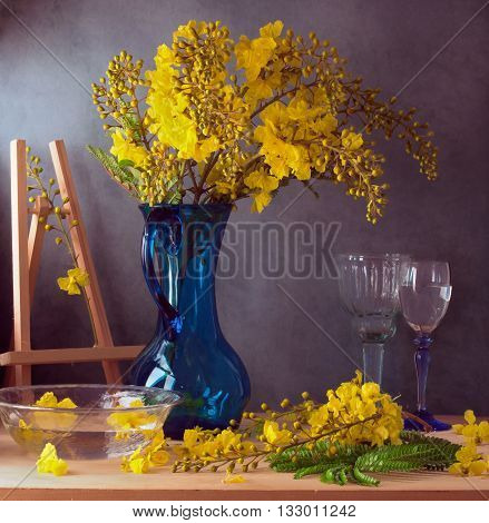 Still life with beautiful yellow flowers in blue glass jug