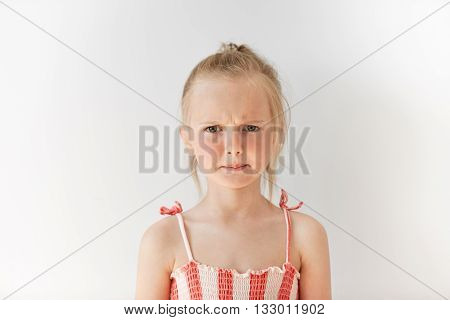 Small Female Child Looking Seriously At Camera In White Studio. Blond Girl With Pony-tail Frowning E