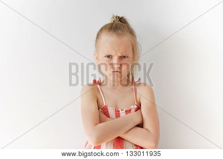 Portrait Of Caucasian Kid With Blond Hair And Crossed Hands On Her Chest. Angry Female Child With Sp