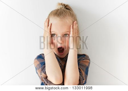 Blond Caucasian Female Child Opening Her Mouth In Astonishment And Clutching Head In Horror. Scared
