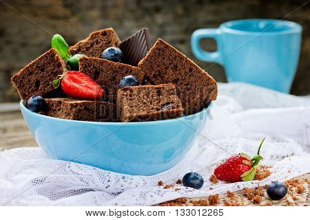 Chocolate brownie cake decorated with strawberry and blueberry selective focus