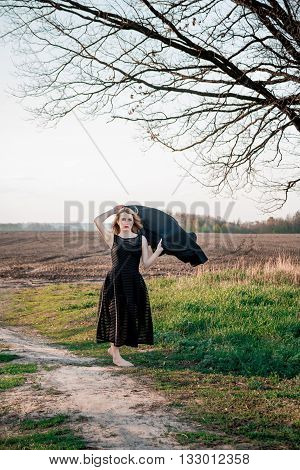 Sad and lonely woman meadow. Beautiful girl in black dress with black scarf in her hands raised above his head outdoors.