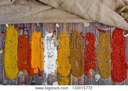 Colourful spices on the table. Various Spices in on wooden background top view. Spices background