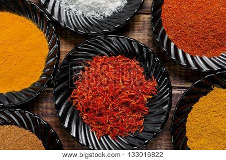 Spices in black ceramic plates on wooden background. Various spices selection. Six plates with different colorful spices top view. Closeup